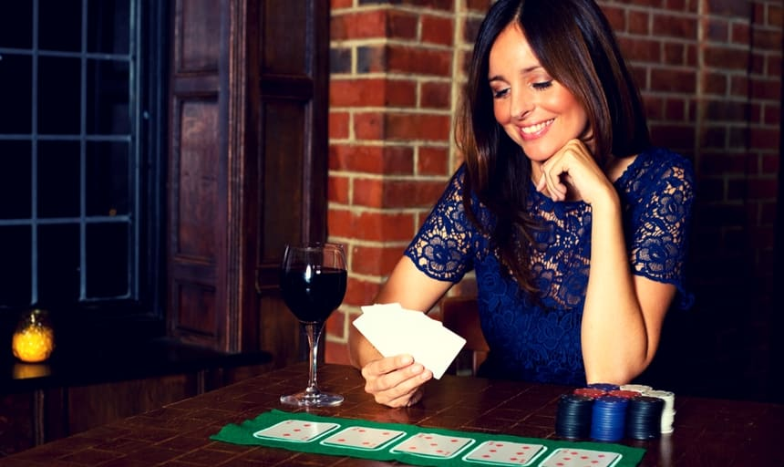 Sexy woman playing cards with a glass of wine
