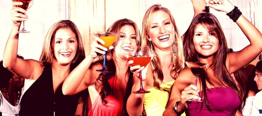 Group of girls having a night out with cocktails