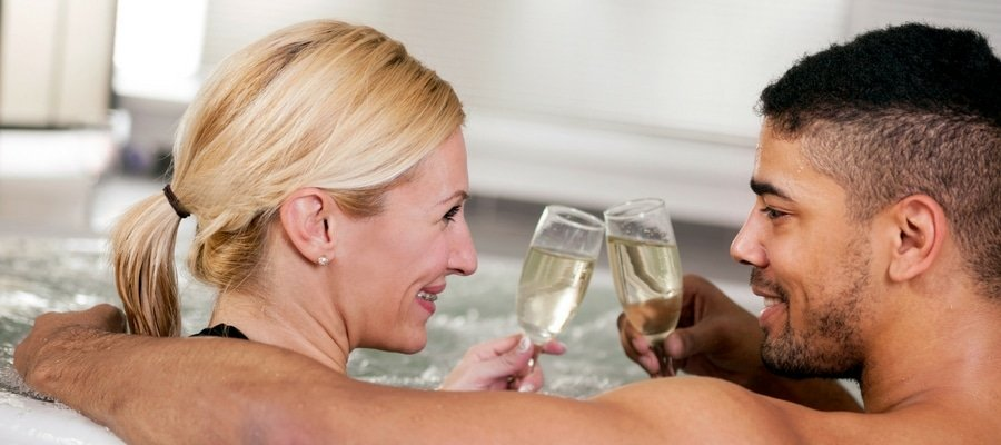 Attractive couple with champagne in spa