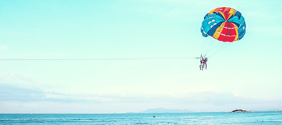 Couple para-sailing over ocean