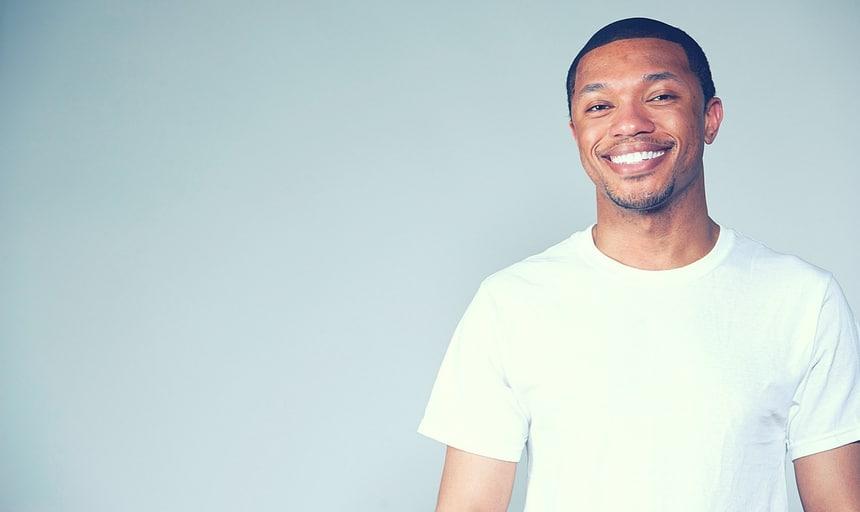 Black man in plain white t-shirt smiling