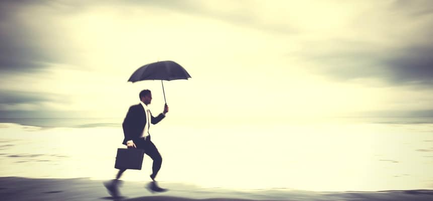 Business man running on beach with umbrella