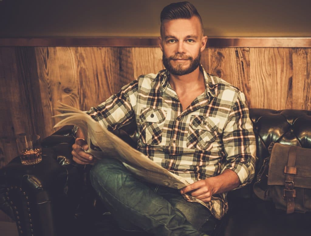 Middle-aged hipster reading newspaper on leather sofa in barber shop