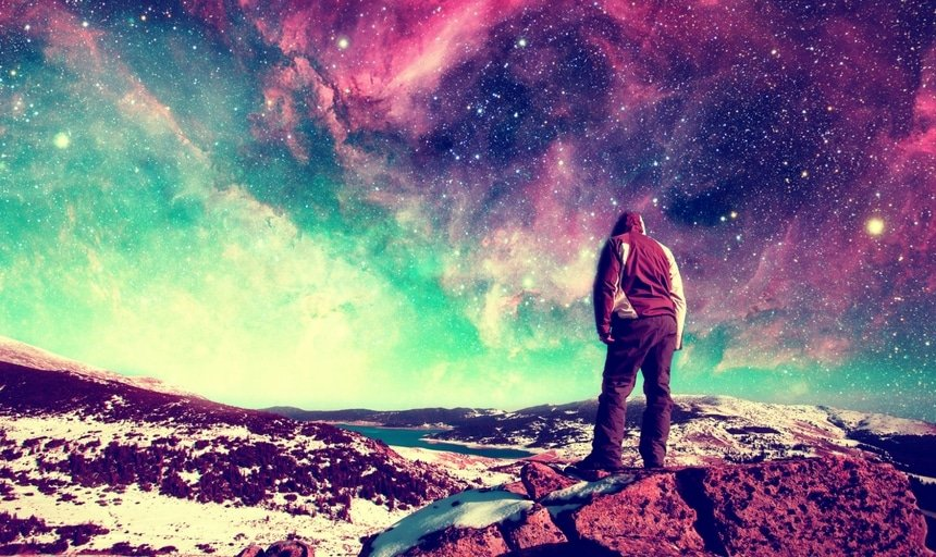 Dreamer standing on the rocks looking at the sky and thinking about his purpose in life