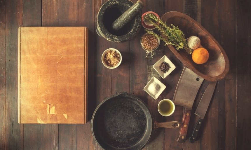 Ingredients and utensils and cookware on wooden bench