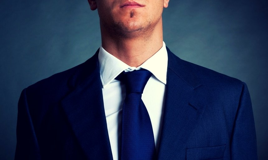 Man closeup with navy tie and navy suit with white shirt