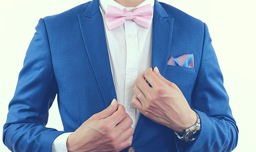 Man in blue suit with pink bow tie and pocket square