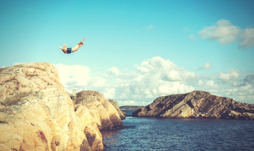 Man jumping off of rock into the water