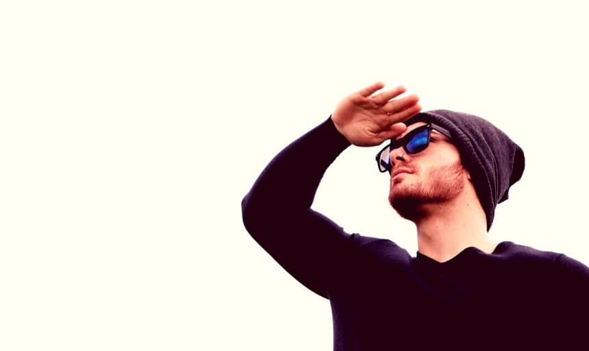 Man looking in distance with thermal shirt on and sunglasses