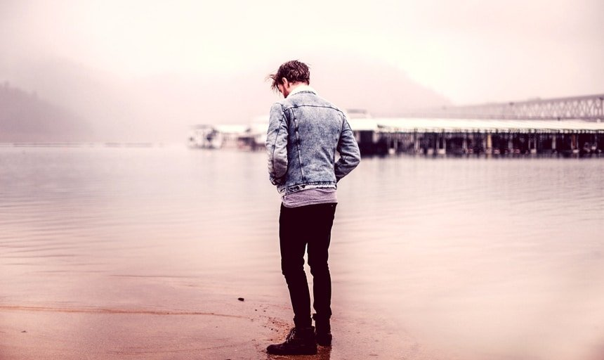 Man near water with denim jacket looking away