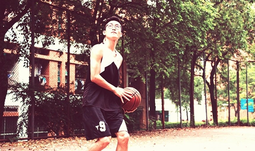 Man playing basketball with glasses in black and white uniform