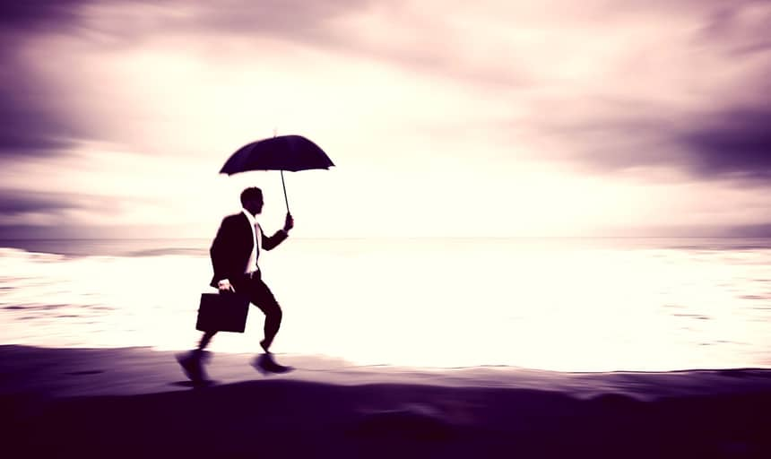 Man running along the beach with umbrella and briefcase