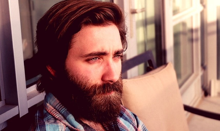 Man with full beard looking into the distance
