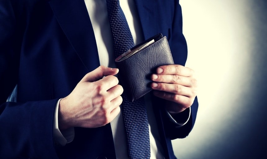 Man with suit holding leather wallet