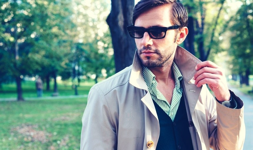 Man with trench coat and sunglasses in park
