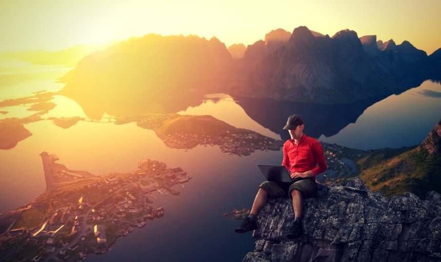 Man working on laptop on cliff with view