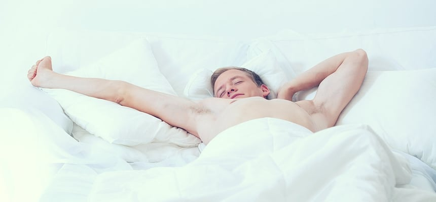 Single man waking up in bed with sheets