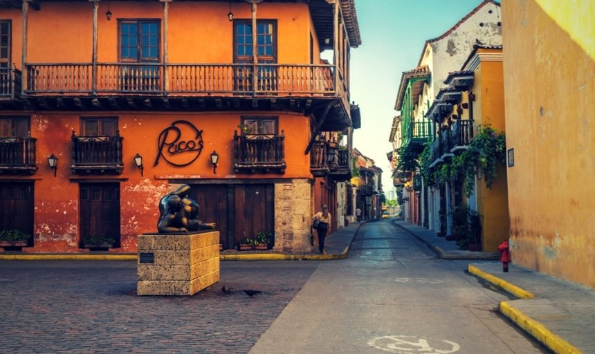 Streets of Cartagena, Colombia in the daytime with woman walking down the street, near Paco's