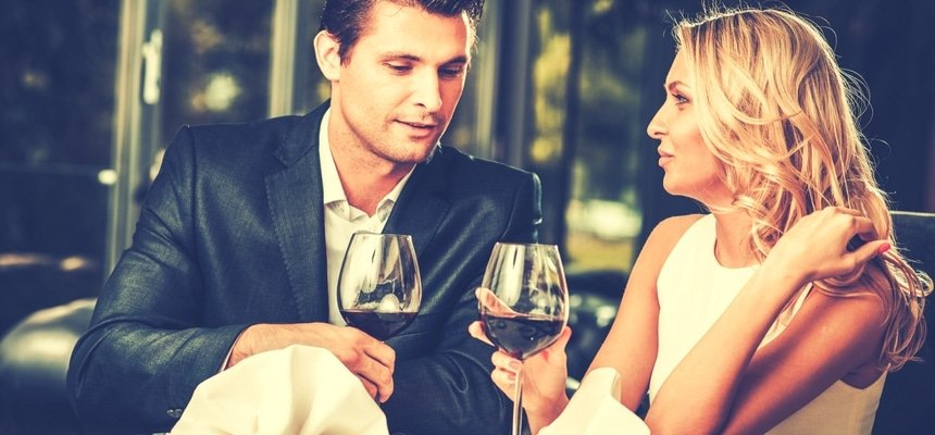Attractive couple on a date in a restaurant with red wine