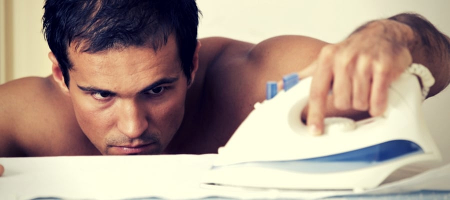 Man concentrating on ironing without a shirt on