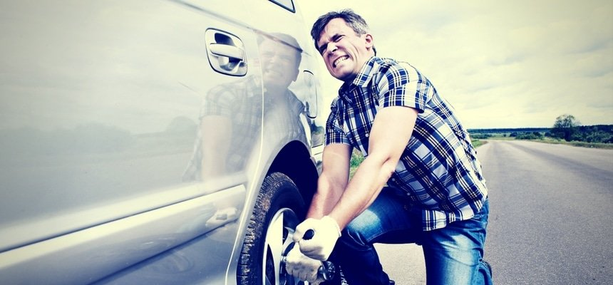 Man struggling to change tire of car