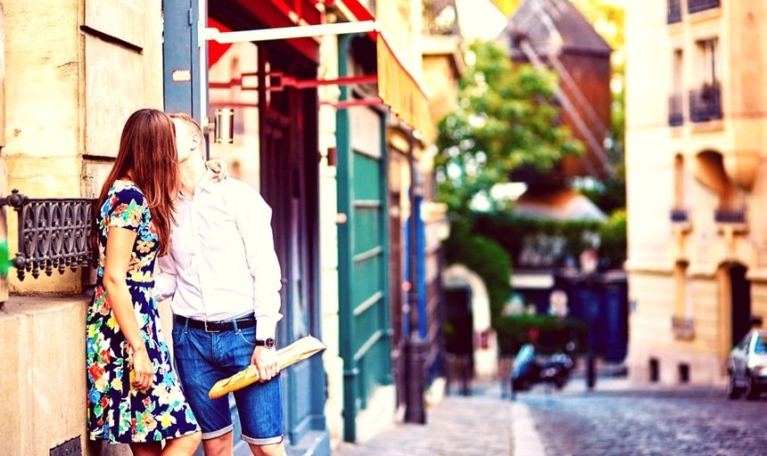 Young romantic couple kissing on Montmartre in Paris holding baguette