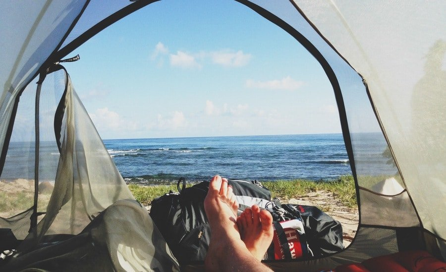 Man's view of ocean from tent