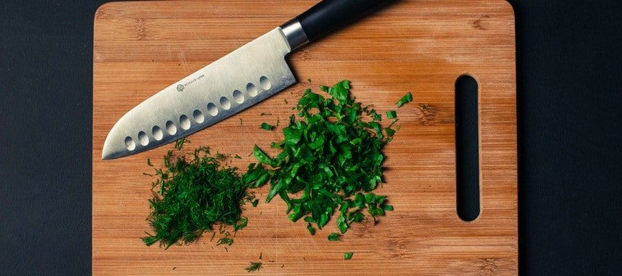 Knife with cutting board and herbs