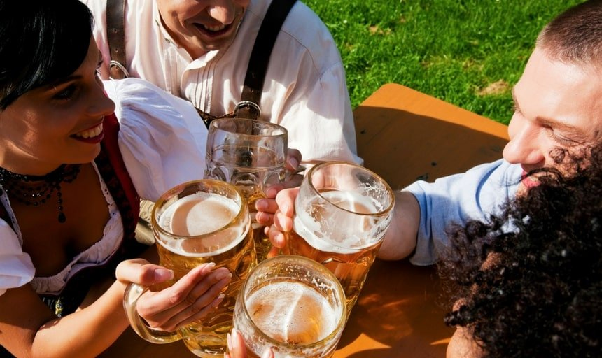 Group of four in traditional Bavarian dress, Lederhosen and Dirndl, drinking beer and smiling