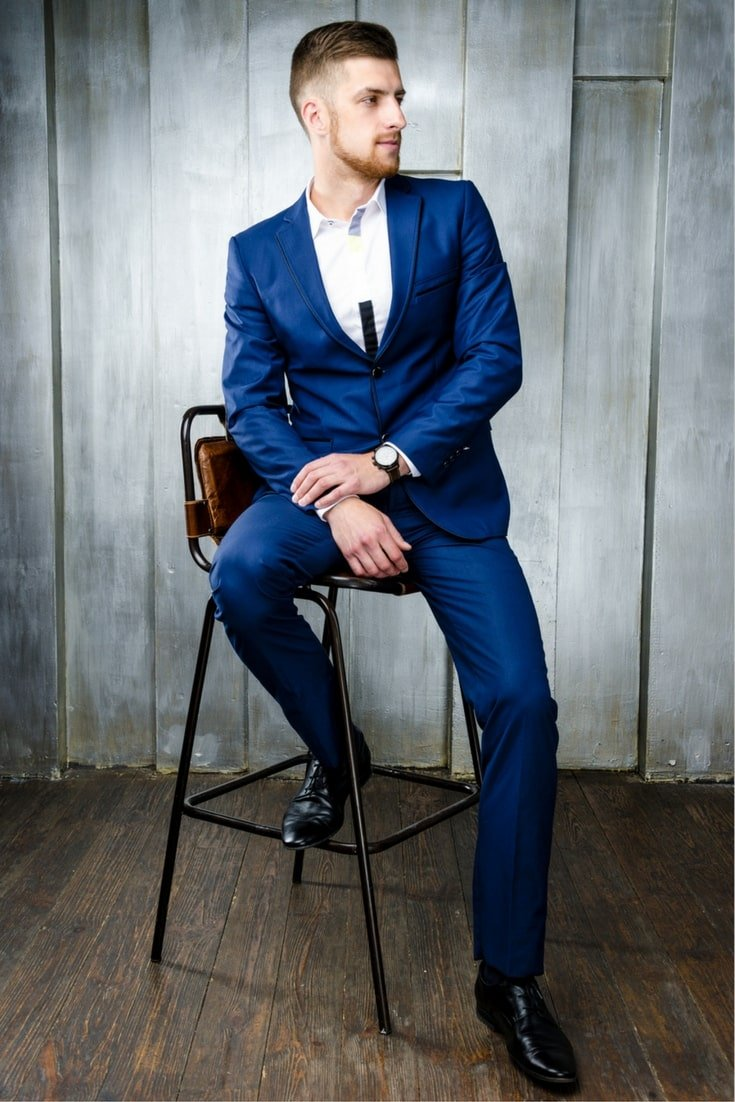 Man in blue suit with black shoes sitting on a stool
