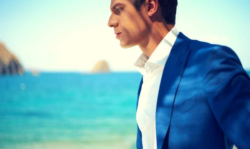 Attractive man in blue suit and white shirt at the beach