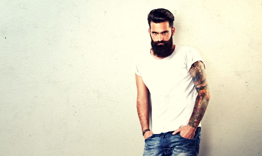 Bearded man with tattoos in white shirt and jeans