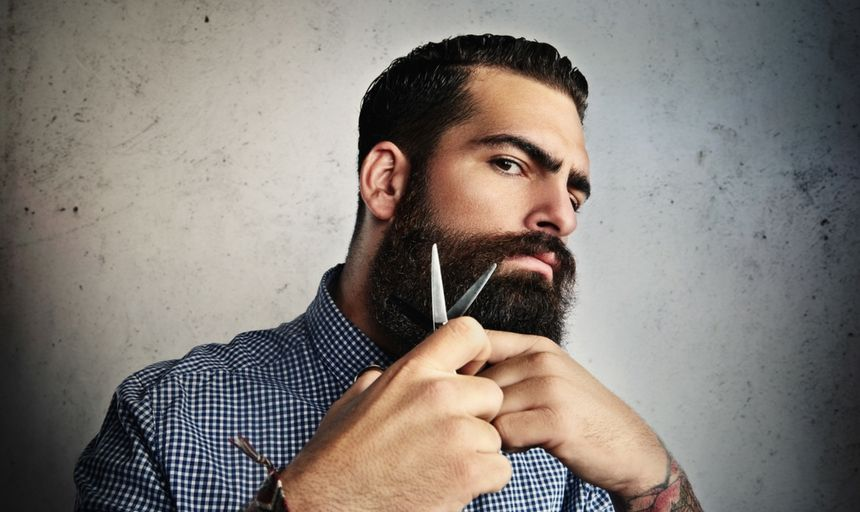 Man cutting beard with scissors with a mean face