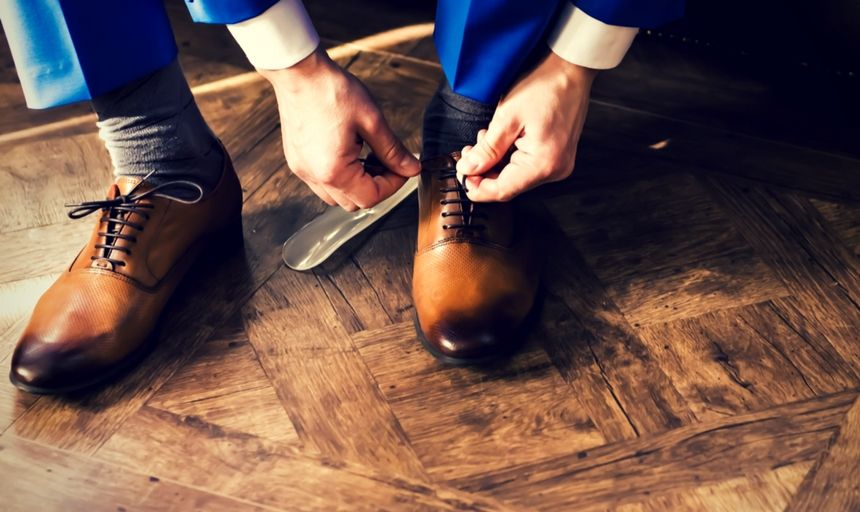 Man in blue seat with tan dress shoes tieing shoe laces