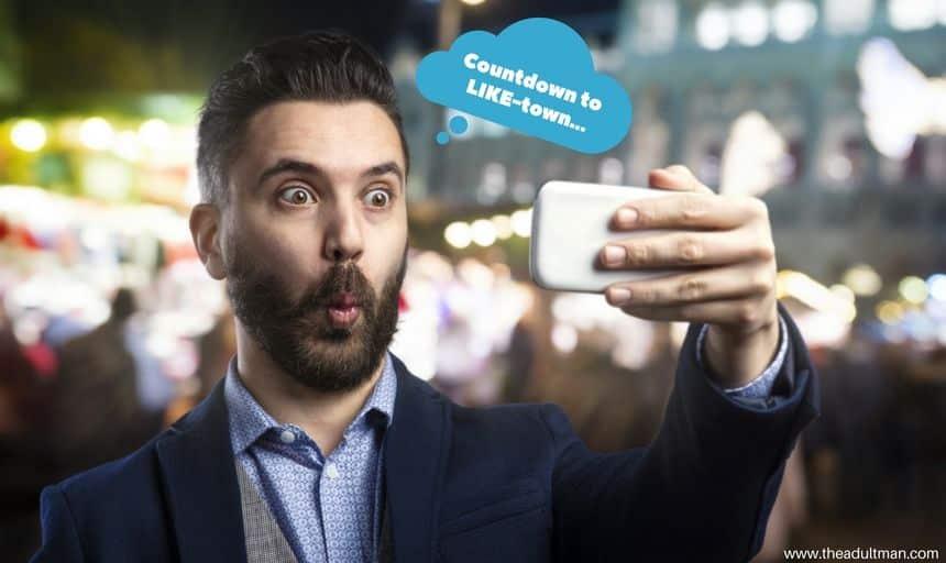Man in suit with beard posing for selfie