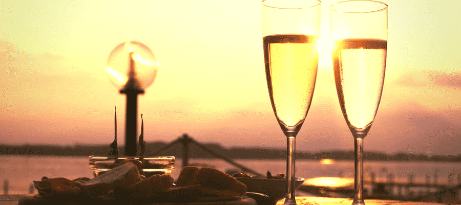 Two glasses of champagne and food near the water