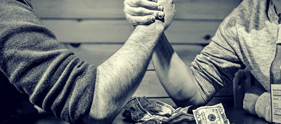 Men arm wrestling for money