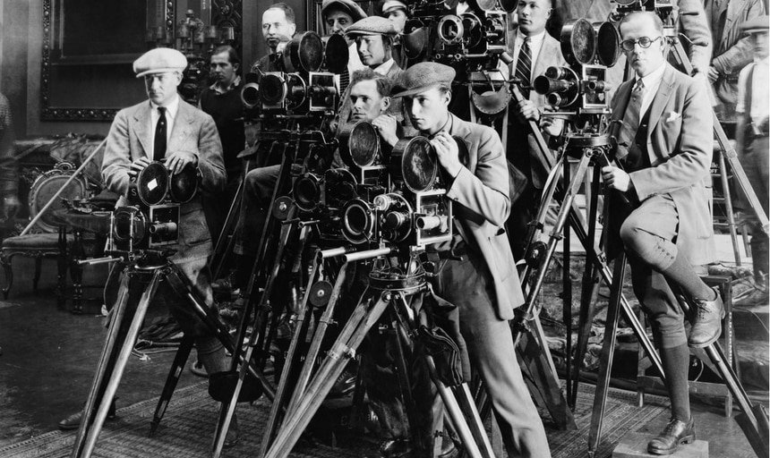 A bunch of photographers in business suits setup behind their cameras - black and white vintage