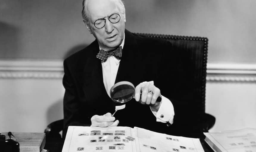 Elderly man in suit and bowtie collecting stamps - black and white vintage
