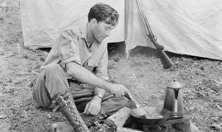 Man cooking outside his tent on a campfire vintage black and white style
