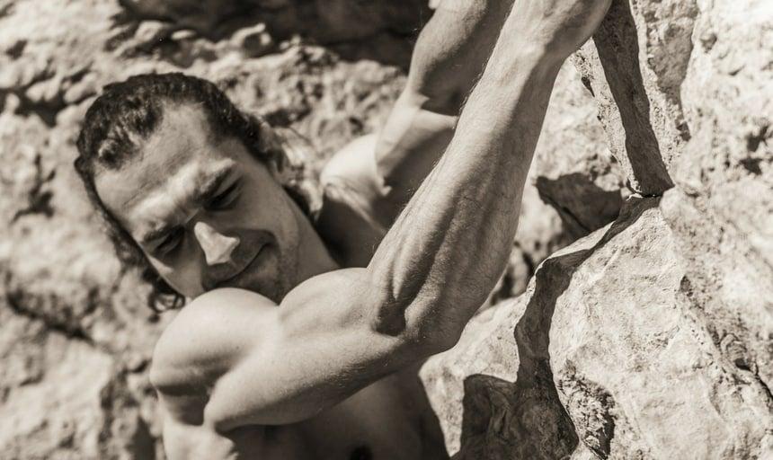 Muscular man rock climbing - vintage style