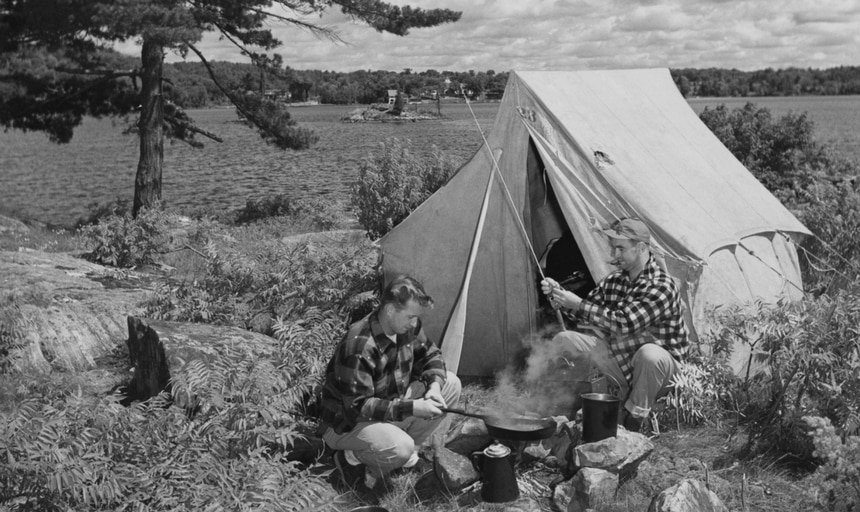 Two men outside camping, one with fishing pole one cooking, next to lake and tent - black and white vintage