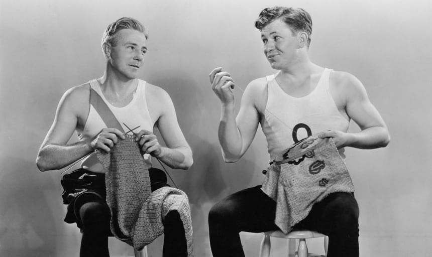 Two men sitting down and knitting while looking at each other and wearing white singlets - black and white vintage