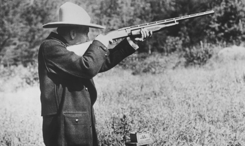Vintage image of man with rifle wearing hat target shooting