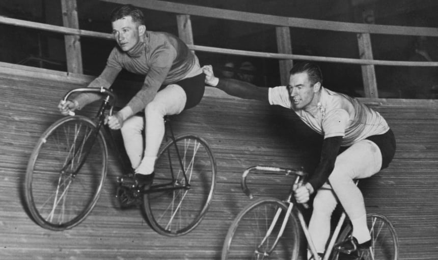 Vintage image of two men cycling, the man behind holding onto the one in front