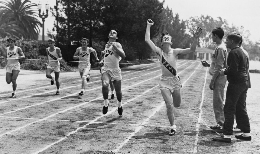 Vintage running race, man straining to get through finish line - black and white