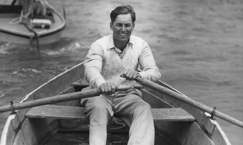 Guy rowing in a rowboat with a jumper on (black and white)