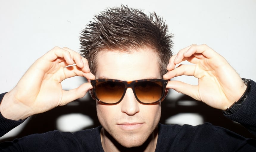 Man with slick hair close up wearing brown sunglasses