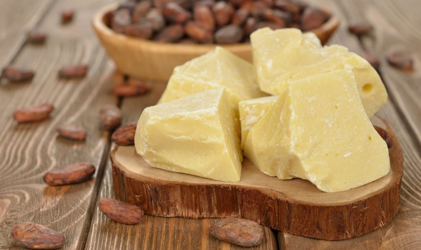 cocoa butter in its natural form on a wooden setting surrounded by cocoa beans