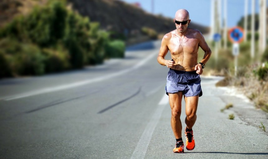Man running shirtless on the side of the road
